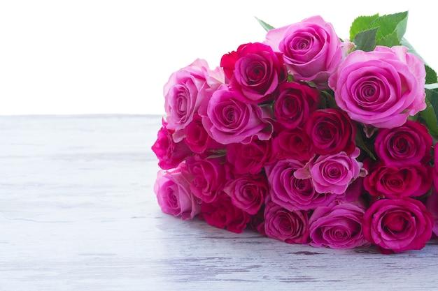 白い背景で隔離のテーブルの境界線上のピンクとマゼンタの新鮮なバラの花束