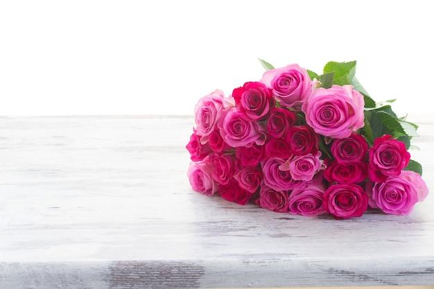 白い背景で隔離の木製のテーブルの境界線上のピンクとマゼンタの新鮮なバラの花束