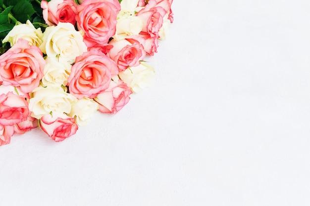 明るい背景にピンクと白のバラの花束。