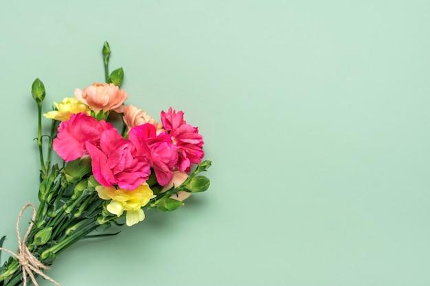 Букет из розовых гвоздик на зеленом фоне вид сверху плоская планировка праздничная открытка 8 марта