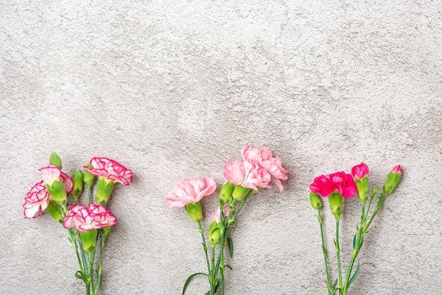 灰色のコンクリート背景にピンクのカーネーションの花の花束