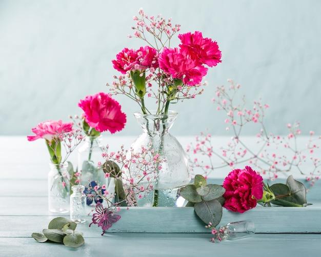 가벼운 청록색 나무 표면에 유리 꽃병에 분홍색 카네이션의 꽃다발. 어머니의 날, 생일 인사말 카드. 공간 복사