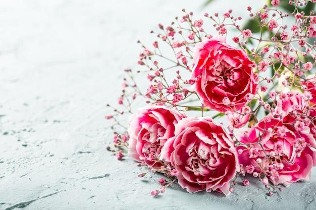 Букет из розовых гвоздик на светло-бирюзовой деревянной поверхности. открытка с копией пространства
