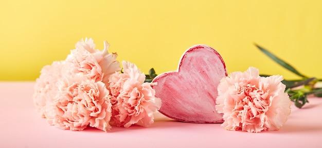 ピンクのカーネーションとハートの飾りの花束