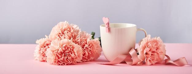 Букет из розовых гвоздик и белая чашка дизайн-концепция праздничного приветствия с букетом гвоздик и ...