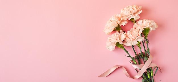 Букет из розовых гвоздик на розовом фоне стола