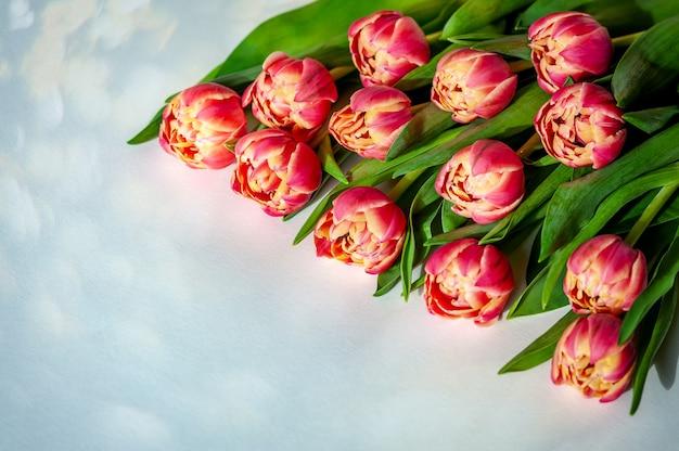 パステル調のテーブルにピンクコーラルチューリップの花束
