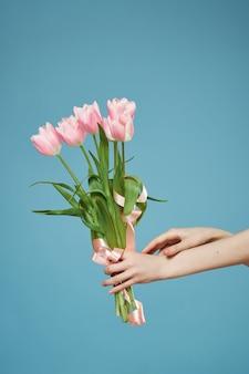 Букет из розовых цветов в руке романтический подарок синем фоне. фото высокого качества