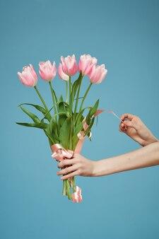 手にピンクの花の花束ロマンスギフト青い背景