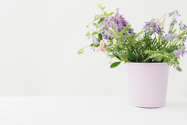 白いテーブルの上に花瓶のピンクの花の花束。テキスト用の空きスペース