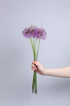 テキストのコピースペースと灰色の背景で隔離の手で背の高い茎にピンクの花の花束