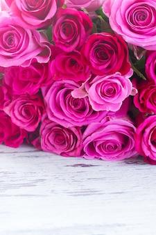 ピンクの新鮮なバラの花束は、白い木製の古い背景にボーダー