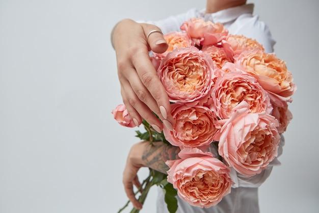 ピンクのメディアの花の花束、バラのタトゥーの花束を持つ少女の手に、母の日、バレンタインデー