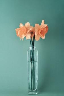Букет из розовых цветов нарцисса в стеклянной вазе на голубом фоне. творческие нарциссы, крупным планом