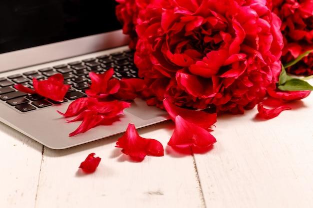 ピンクの牡丹、ラップトップ、スマートフォン、ペン、メガネ、白いテーブルの上のノートの花束