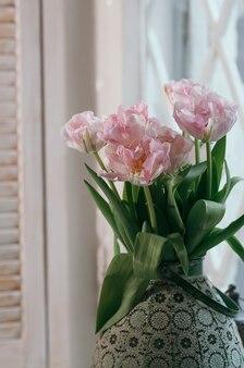背景の窓枠ライト木製ジャロジーの古い大きな花瓶にピンクの牡丹チューリップの花束
