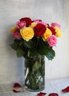 白のガラスの花瓶にピンク、赤、黄色のバラの花束。