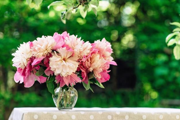 Букет из розовых пионов романтические цветы в стеклянной вазе на столе.