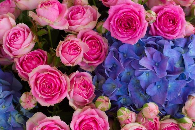 Букет из розовых роз и цветов голубой гортензии крупным планом