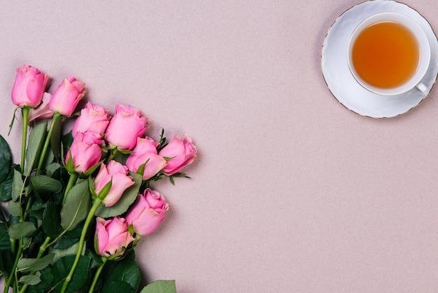 ピンクのバラの花束とピンクの背景にお茶のカップ。コピースペースのあるフラットレイ。