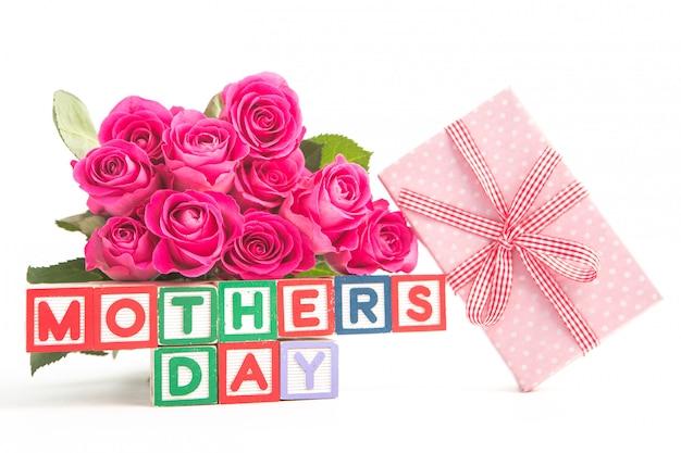 다른 색상 맞춤법 어머니의 날의 나무 블록 옆에 분홍색 장미와 분홍색 선물 꽃다발