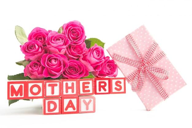 어머니의 날 맞춤법 나무 블록 옆에 분홍색 장미와 분홍색 선물 꽃다발