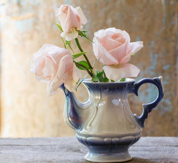 素朴なスタイルのヴィンテージのティーポットでピンクのバラの花束