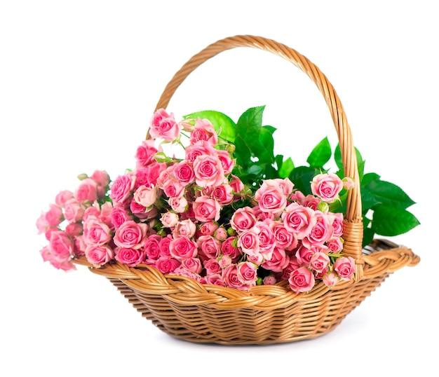 白い背景で隔離のバスケットのピンクのバラの花束