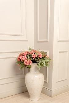 고전적인 스타일의 바닥 세라믹 꽃병에 핑크 장미 꽃다발. 쉬비 시크한 인테리어 장식.