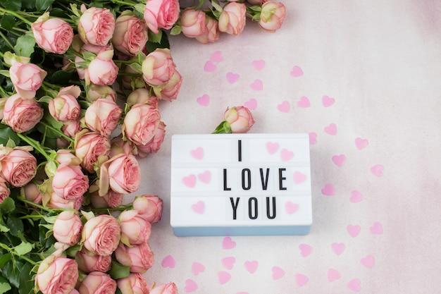 Букет из розовых роз, розовые сердечки и тарелка с надписью: я тебя люблю