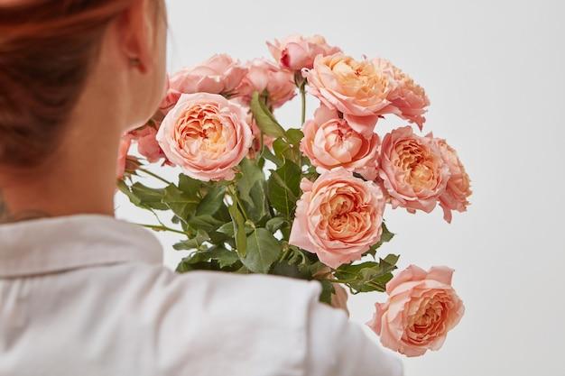 ピンクのバラの花束。花の花束を持っている女の子の後ろからの眺め。聖バレンタインデー