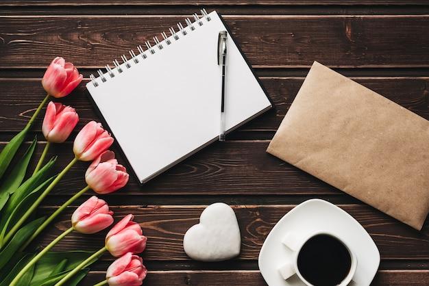 ピンクのチューリップの花と木製の茶色のテーブルの上のコーヒーカップの花束
