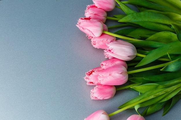 Букет из розовых тюльпанов на сером фоне плоской планировки.