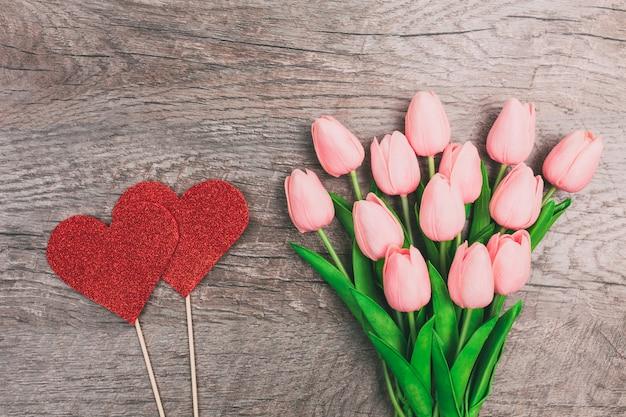 ピンクのチューリップと木製の背景に、紙から赤い2つの心の花束