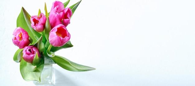 Букет розовых тюльпанов в стеклянной вазе на светлом фоне с местом для текста
