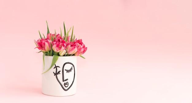 분홍색 배경에 흰색 꽃병에 핑크 튤립 꽃다발