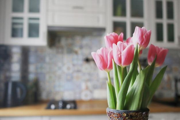 明るいキッチンにピンクのチューリップの花束。