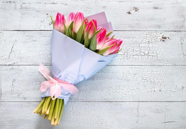 Букет розовых тюльпанов на деревянных фоне