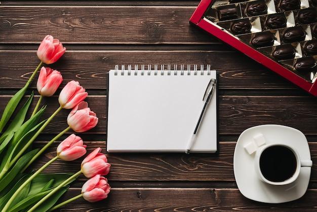 一杯のコーヒーと木製のテーブルにチョコレートの箱とピンクのチューリップの花束