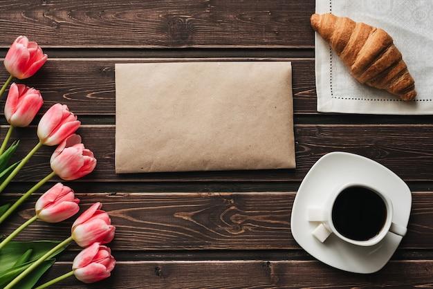 Букет из розовых тюльпанов с чашкой кофе и круассаном