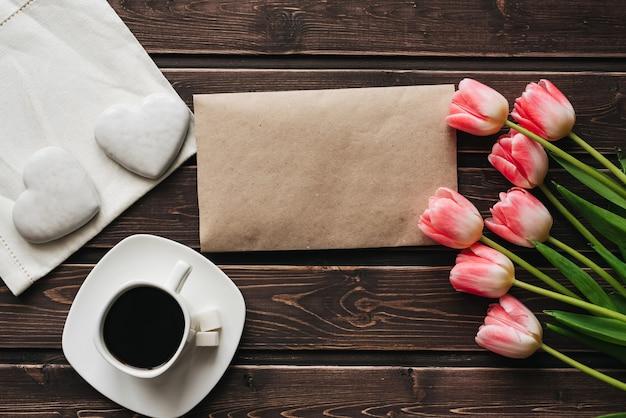 一杯のコーヒーとハートの形をした白いジンジャーブレッドとピンクのチューリップの花束