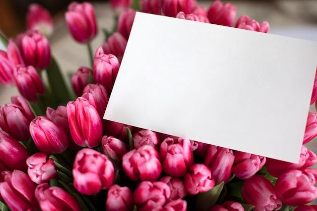 メモ付きのピンクのチューリップの花束。女性の日のグリーティングカード。