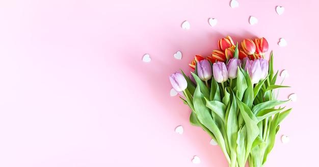 柔らかなパステル調の明るい背景に装飾的なハートが散りばめられたピンクのチューリップの花束。上面図。バレンタインデーのお祭りの背景。