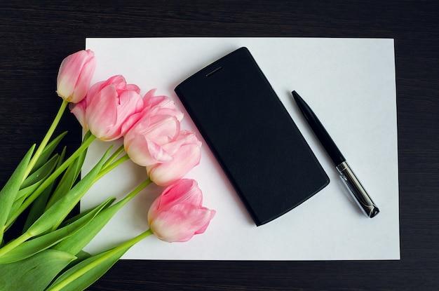ペンと携帯電話でピンクのチューリップの花束
