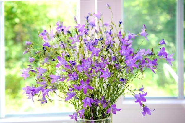 Букет фиолетовых колокольчиков на подоконнике летом