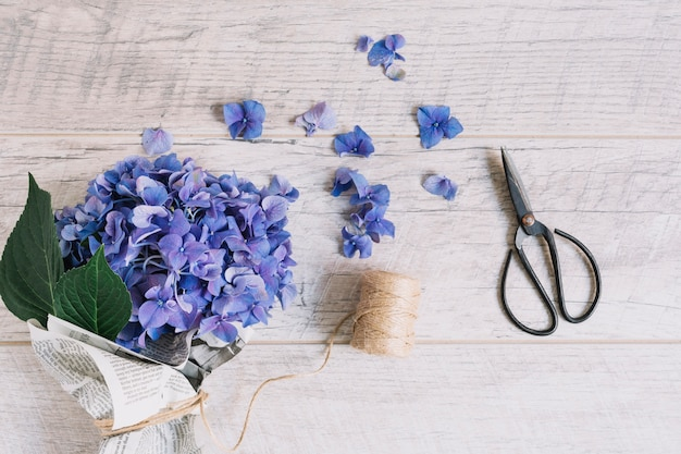 나무 테이블에 스풀과 가위로 묶인 보라색 수국 꽃의 꽃다발