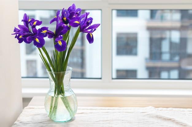 Букет фиолетовых ирисов в прозрачной стеклянной вазе