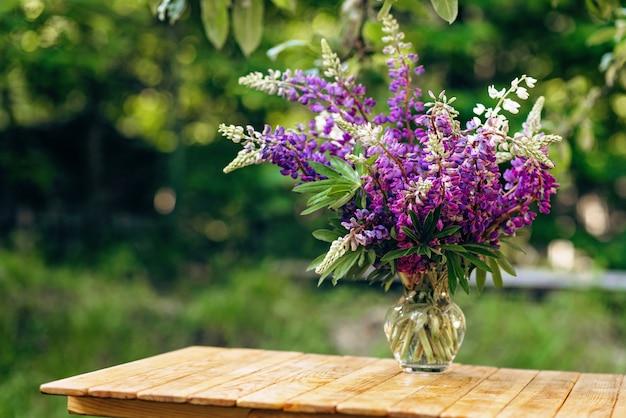Букет из фиолетовых цветов люпина в стеклянной вазе
