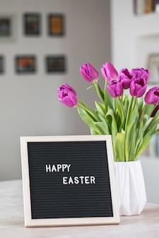행복 한 부활절 단어와 보라색 튤립 꽃과 편지 보드의 꽃다발