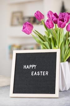 紫色のチューリップの花とハッピーイースターの言葉で文字板の花束 Premium写真